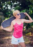 Beautiful young girl with skate board wearing sunglasses stock image