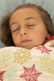 Beautiful young girl sleeping under a snowflake blanket Royalty Free Stock Photography
