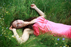 Beautiful young girl sleeps on the meadow in green grass Stock Images