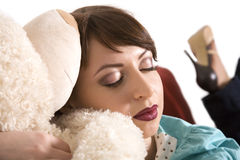 The girl sleeps with a teddy bear. The beautiful young girl sleeps on sofa with a teddy bear on a white background royalty free stock image