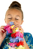 Beautiful young girl smelling a paper lei eyes closed Royalty Free Stock Image