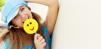 Beautiful young girl with a smile, with great candy in the hands of a Sunny day stands near the wall stock photo