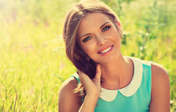 Beautiful young girl with a smile. Lying on the field on the grass, enjoying nature Stock Photos