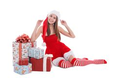 A girl sitting elbow on gifts with raised hands on a white isolated background Stock Photos