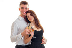 Beautiful young girl smiling closing her eyes stands next to a cute guy and they are holding wine glasses Stock Photo
