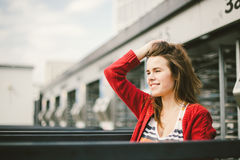 Beautiful young girl smiling, is happy, happy in a hat, a red shirt over city Royalty Free Stock Photos