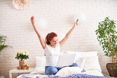 Beautiful young girl smiling and holding a Bank card and laptop on the bed royalty free stock photography