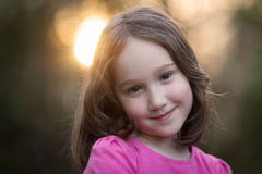 Beautiful Young Girl Smiling at Sunset. A beautiful young girl looking at the camera while the sun sets in the background Stock Photo