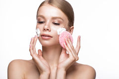 Beautiful young girl with sponge and foam cleanser, French manicure. Beauty face. Beautiful young girl with sponge and foam cleanser and French manicure. Beauty stock image