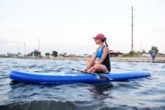 Young girl in sportswear sitting on a SUP board. Beautiful young girl in sportswear sitting on a SUP board stock photo
