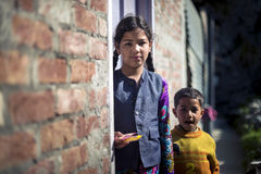Beautiful young girl stand outside home door holding her brother. Royalty Free Stock Photo