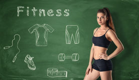 Beautiful young girl standing on the background with fitness sketches. Stock Images