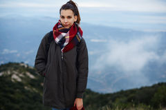 A beautiful young girl standing on the edge of a cliff wrapped in a scarf Royalty Free Stock Images