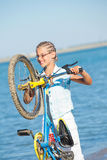 Beautiful young girl standing with her bicycle Stock Image