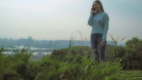 Beautiful young girl standing on the hill and talking on the phone. stock images