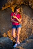 Young girl standing, leaning against a stone wall at sunset with a cocktail in her hand royalty free stock photos