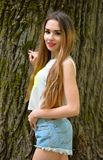 Beautiful young girl standing by an old big tree in the Park. stock image