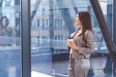Beautiful young girl standing by the window Stock Image