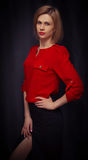 Beautiful young girl stands on a black background. In red blouse Stock Photos
