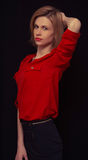Beautiful young girl stands on a black background. In red blouse stock images