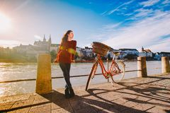 A beautiful young girl stands on the embankment near a city bicycle with a basket of red in Switzerland, the city of Basel. Sunny royalty free stock photo