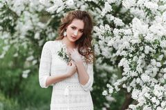 A beautiful young girl stands among the flowering trees. royalty free stock images