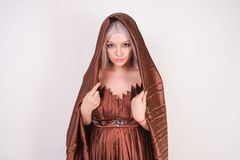 A beautiful young girl stands in a luxurious evening brown pleated dress with a cloth covering her hair and head on white backgrou. Nd in the Studio alone stock images