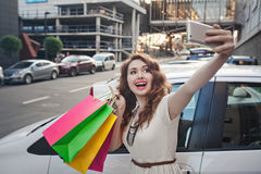 Beautiful young girl stands near a white car, makes a shopping, selfie Stock Image