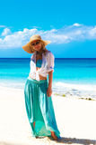 Beautiful young girl in a straw hat on a tropical beach Royalty Free Stock Photos