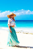 Beautiful young girl in a straw hat on a tropical beach Royalty Free Stock Image