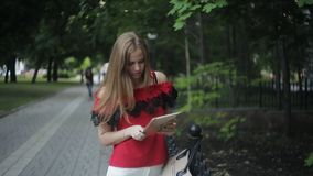 Beautiful young girl received a message from the social network. outdoors with tablet in hand writing sms. Beautiful young girl on the street with a tablet in stock video