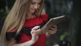 Beautiful young girl received a message from the social network. outdoors with tablet in hand writing sms. Beautiful young girl on the street with a tablet in stock footage