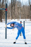 Beautiful young girl stretches on a sports field in winter again Royalty Free Stock Photos