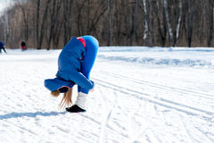 Beautiful young girl stretches on a sports field in winter again Stock Images