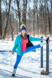 Beautiful young girl stretches on a sports field in winter again Royalty Free Stock Photography