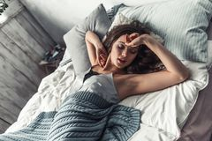 Girl in bed. Beautiful young girl is stretching and yawning after having a nap in bed at home Royalty Free Stock Photo