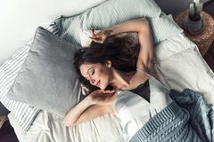 Girl in bed. Beautiful young girl is stretching and yawning after having a nap in bed at home Stock Photos