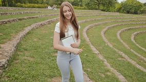 Beautiful young girl student with textbooks and notes smiling strolling through a large green stadium. Rest during study stock footage