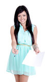 Beautiful young girl. In studio offering pen and paper to sign a contract or sign up and smiling Stock Image