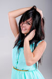 Beautiful young girl. In studio playing with hair and smiling Stock Images