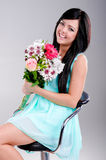 Beautiful young girl. In studio sitting with flowers and smiling Stock Image