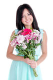 Beautiful young girl. In studio standing with flowers and smiling looking surprised Royalty Free Stock Images