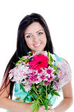 Beautiful young girl. In studio standing with flowers and smiling looking surprised Royalty Free Stock Image