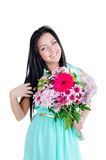 Beautiful young girl. In studio standing with flowers and smiling looking surprised Stock Image