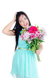 Beautiful young girl. In studio standing with flowers and smiling looking surprised Royalty Free Stock Photos