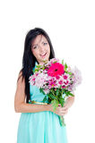 Beautiful young girl. In studio standing with flowers and smiling looking surprised Stock Images