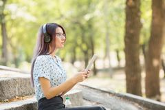 Beautiful young girl studying on a tablet on a park background. Self-education concept. Copy space. Fantastic young student female in headphones watching Stock Photography