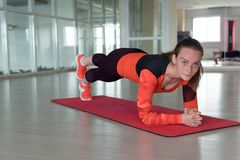 Charming sportswoman trains in the gym stock photography