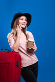 Beautiful young girl with a suitcase and a coffee on a blue background. Going travel Royalty Free Stock Photography