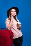 Beautiful young girl with a suitcase and a coffee on a blue background. Going travel Stock Photo